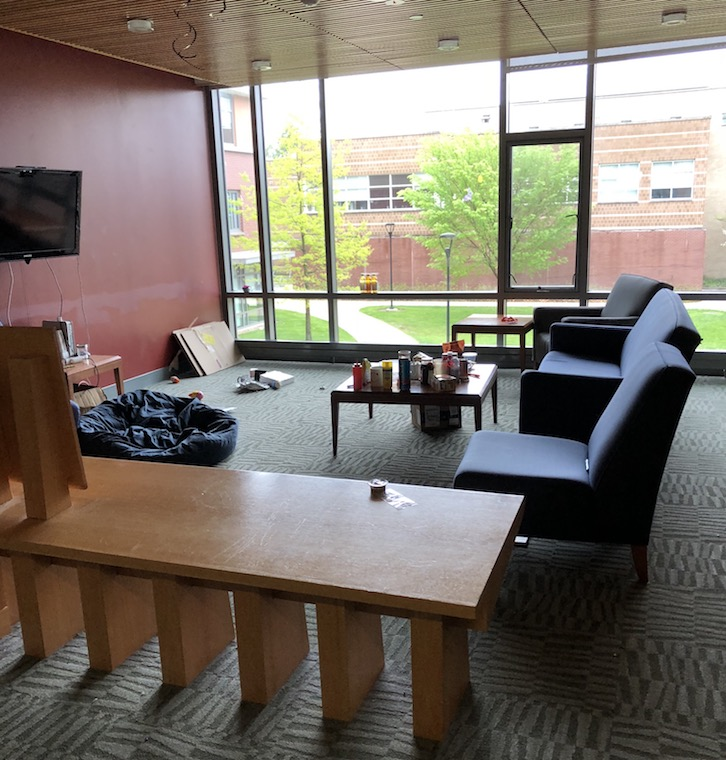 A dorm lounge, featuring chairs, tables, a TV, and a large window. Through the window, trees and the side of another building can be seen.