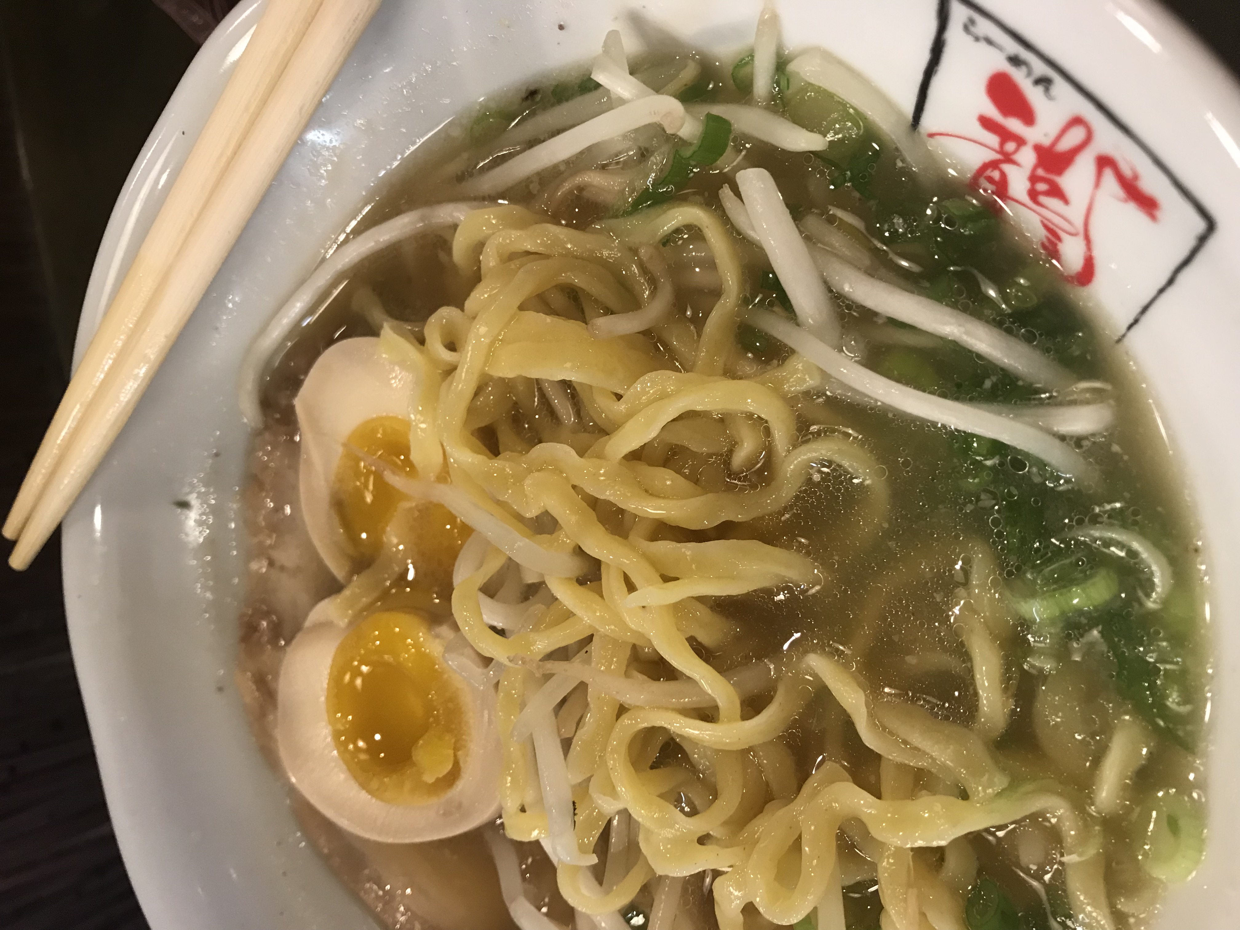 A bowl of ramen with chopsticks on the edge of the bowl.