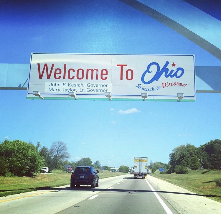 "Blue arch over highway with a sign that reads ""Welcome to Ohio: So much to Discover! John R Kasich, Governor Mary Taylor, Lt. Governor"""