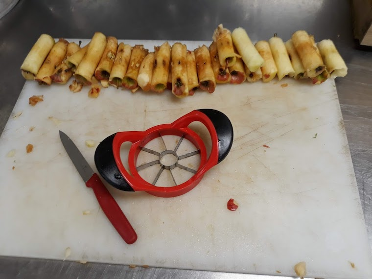 A row of apple cores ona cutting board next to an apple slicer.