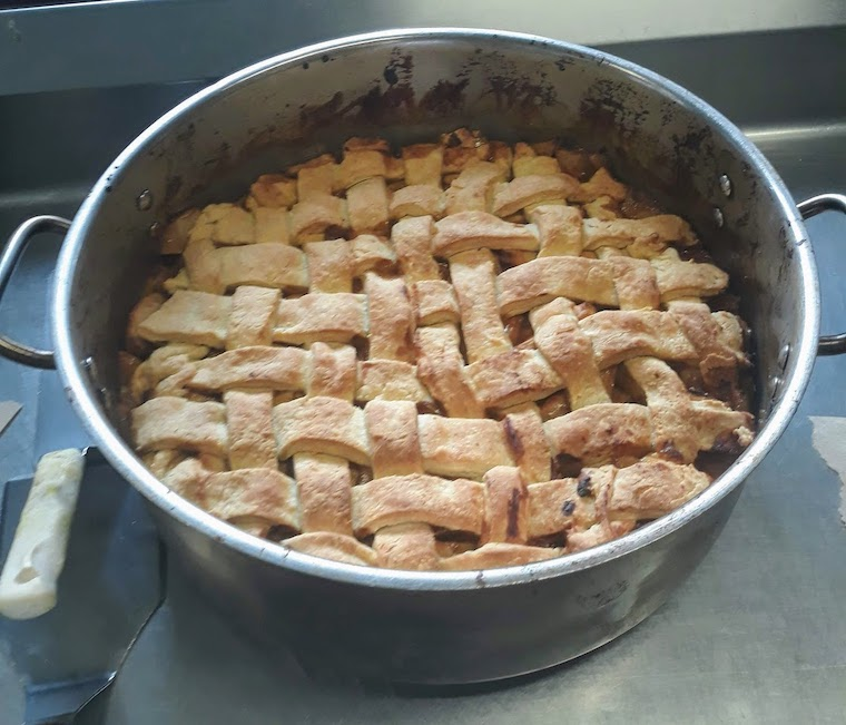 A very large apple pie with a lattice top baked in a soup pot
