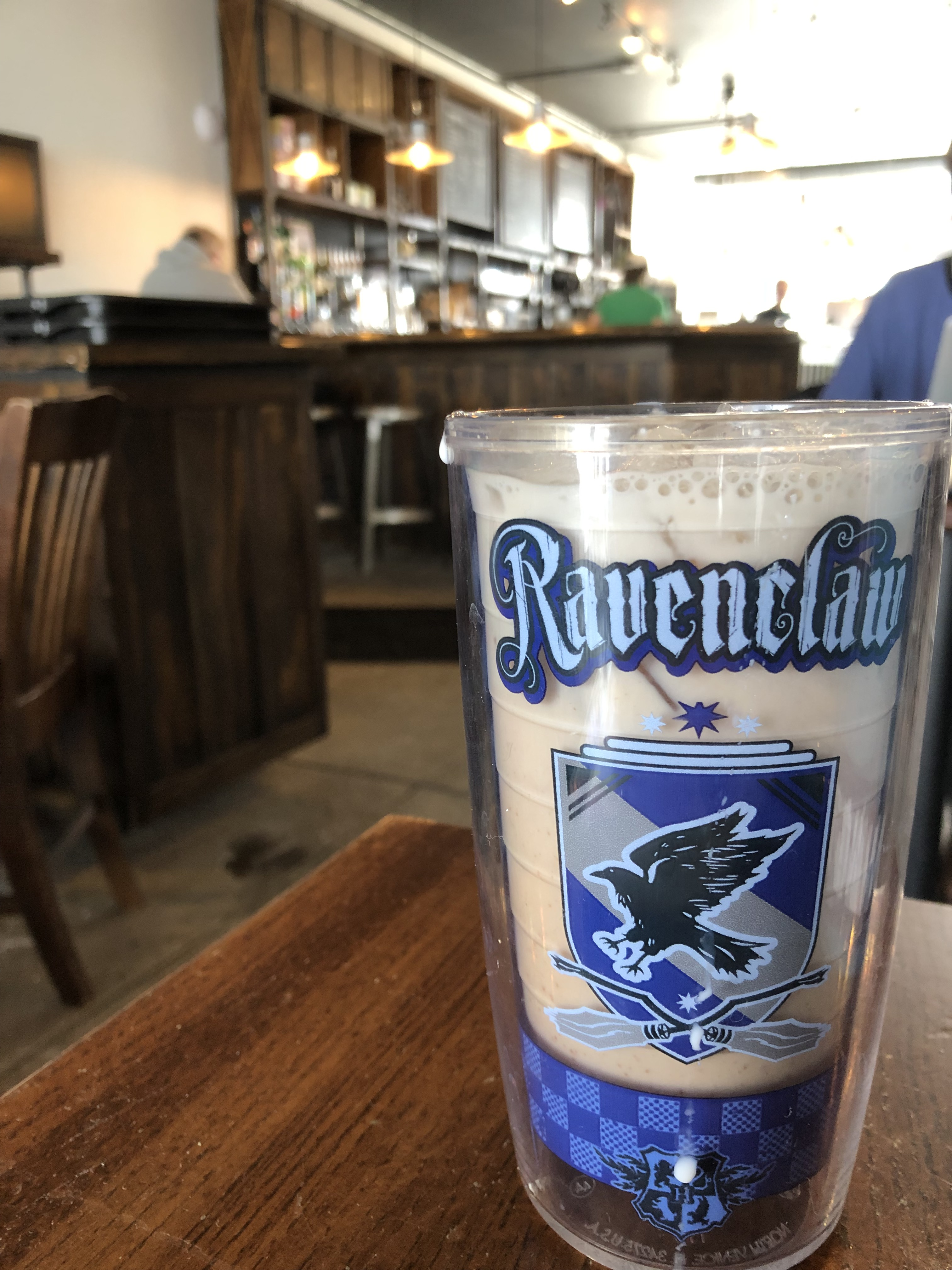 A milky chai latte with small cubes of ice sits in a blue reusable cup with 'Ravenclaw' written across it in blue letters, with the Harry Potter crested below it. Behind the drink are hanging lights and a dark brown, rustic-looking counter and silver stools.