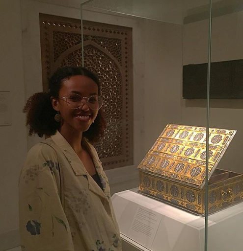 Muntaha stands in front of a gold art display a the Metropolitan Museum of Art.