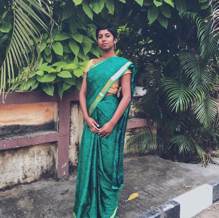 Deborah wearing a green sari, standing tall.