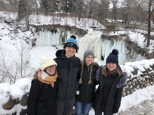 Ilana, Drew, Ciara, and Makaela stand in front of Minnehaha Falls, a frozen waterfall, in full winter gear