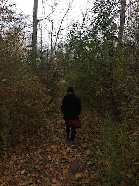 My mom walking along a tree-lined path