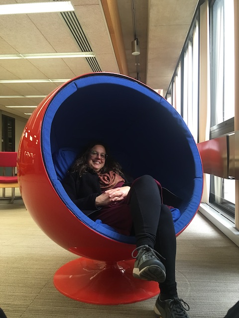 My mom in a bowl-shaped womb chair in the library