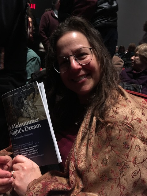 My mom holding up the opera program in the theater