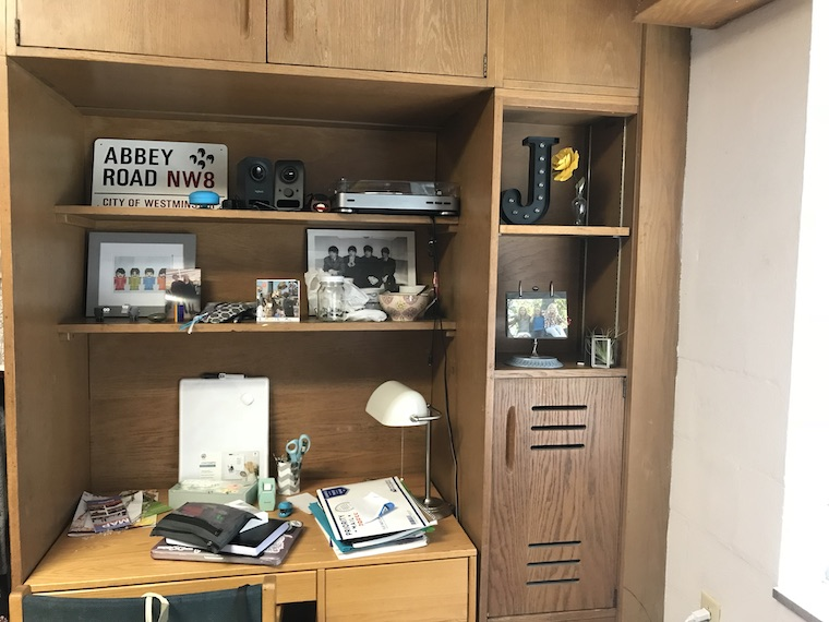 A wooden desk is surround by wooden built in shelves. On the desk are notebooks, a desk lamp, various school supplies, and a whiteboard. On the shelves are bowls, mugs, and silverware; framed art and photos, a record player, and other small mementos.