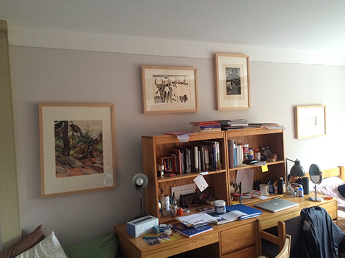 Desk and shelf with books and papers. The wall has 4 framed art works.