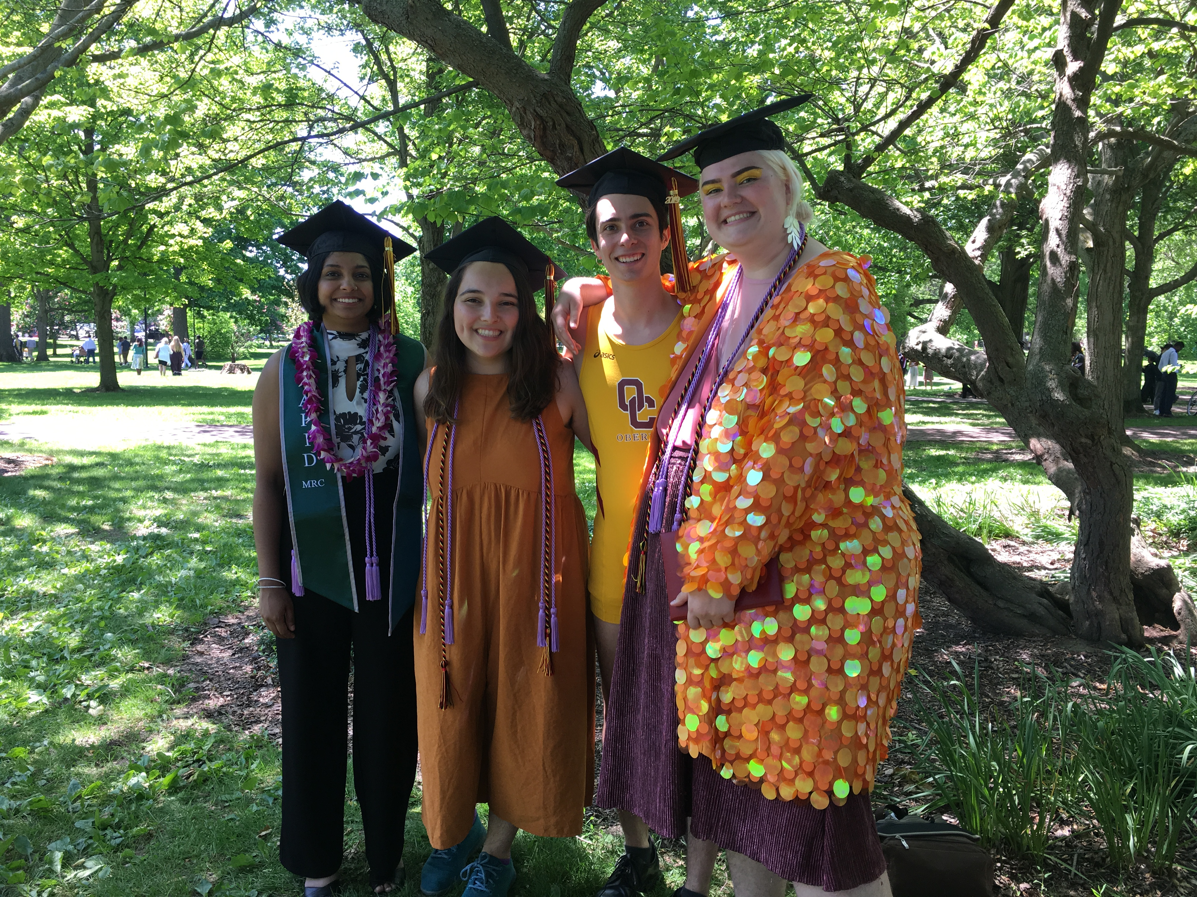 Kira and friends standing in grassy area at graduation. Photo
