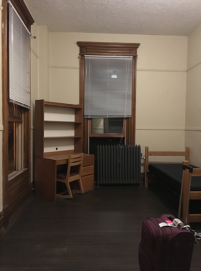 A room with 2 windows is empty, except for a desk, bed, and steam radiator. There is a suitcase in the foreground.