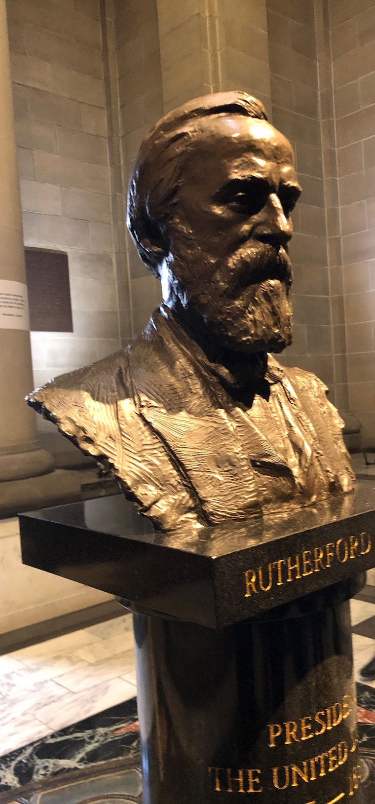 A photo of the bronze-colored bust of Hayes in the room that was the original museum.