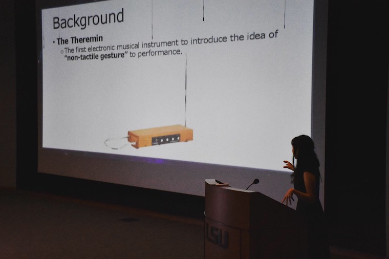 A girl presenting a PowerPoint presentation on stage.