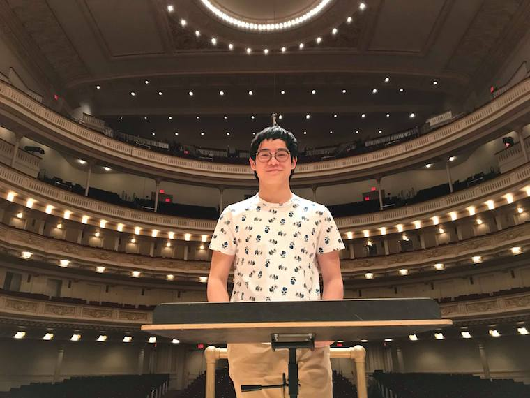 A male student stands on the stage of Carnegie Hall.