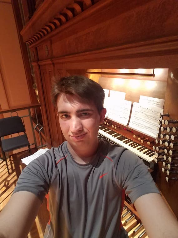 A male student sitting in front of the Finney Chapel organ.