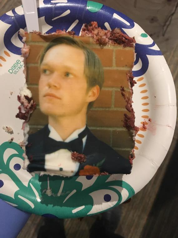 A piece of cake with a male student on it.