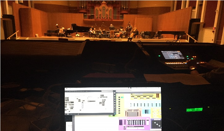 A computer on a table with a small sinfonietta on a stage in the distance.