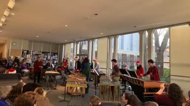 A bunch of percussionists playing marimbas. Holiday decorations.
