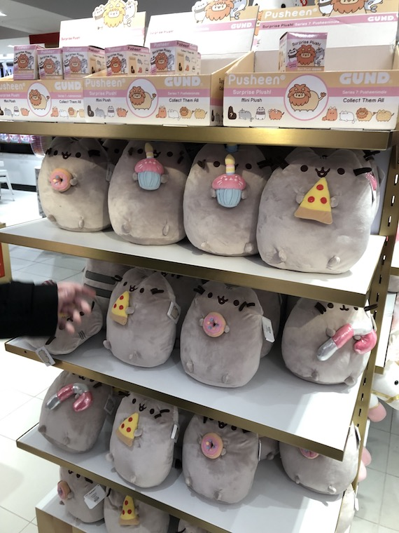 A shelf full of Pusheen the cat plushies.