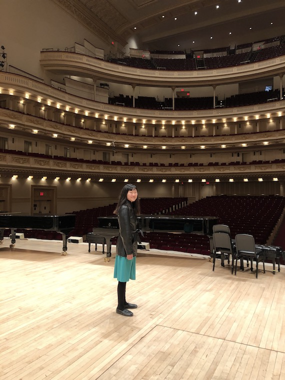 A girl standing alone on Carnegie's stage.