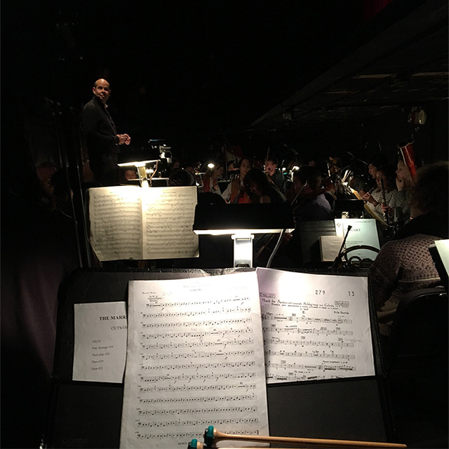 My view from the pit: timpani, music, other musicians in the orchestra.