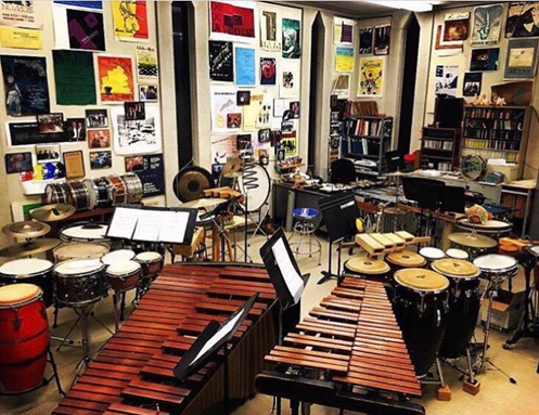 Percussion studio with cymbals, drums, marimbas, and timpani.