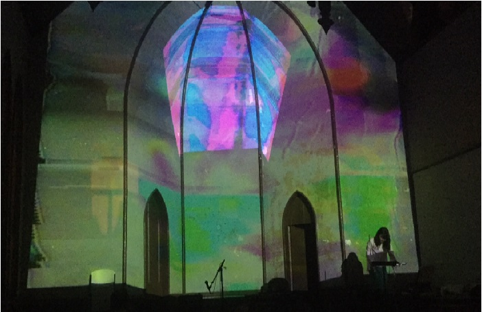 A girl playing a theremin in a church.