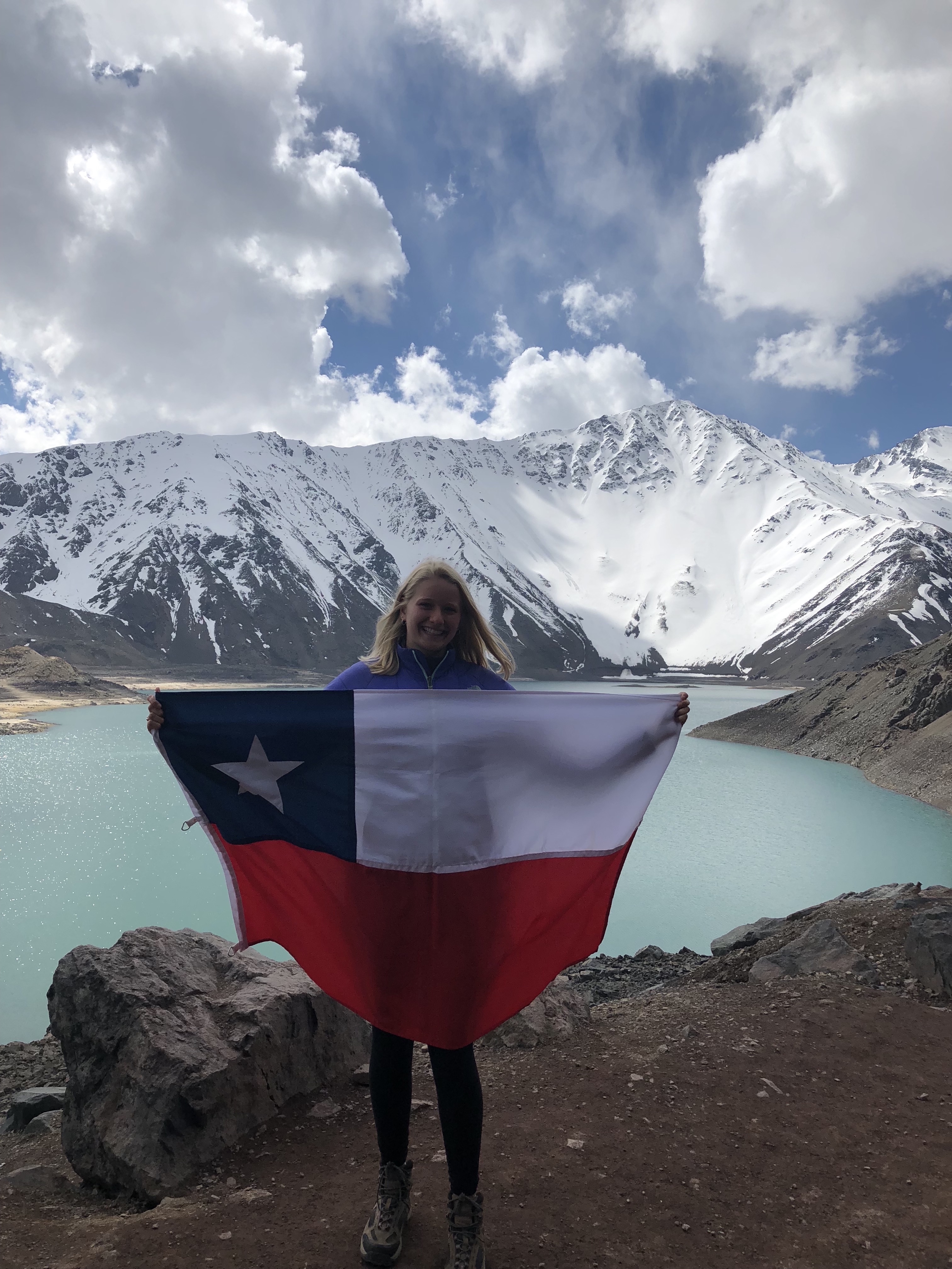 Sarah holds a Chilean flag with mountains and a lake in the background