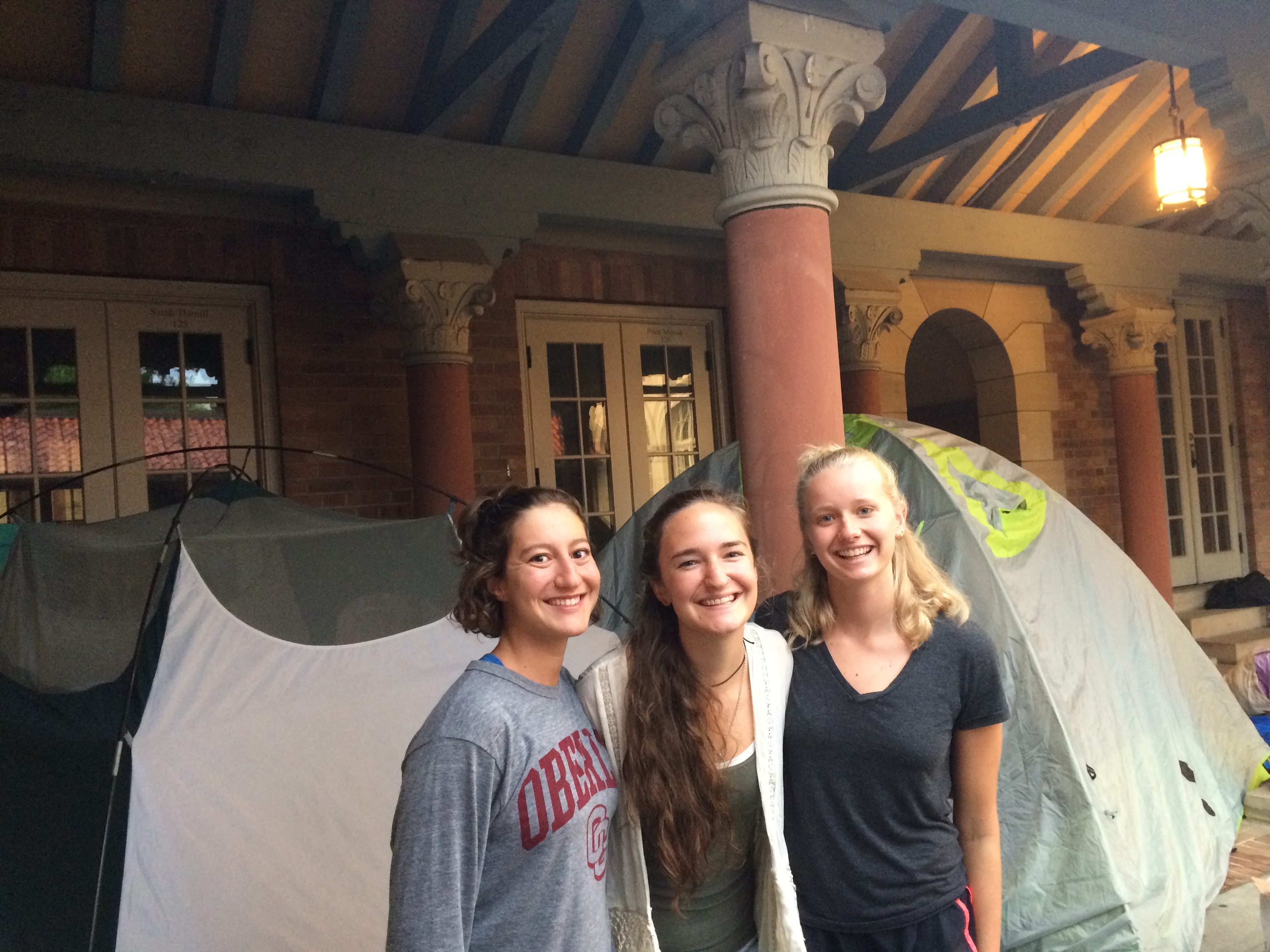 three college students stand smiling in front of a tent