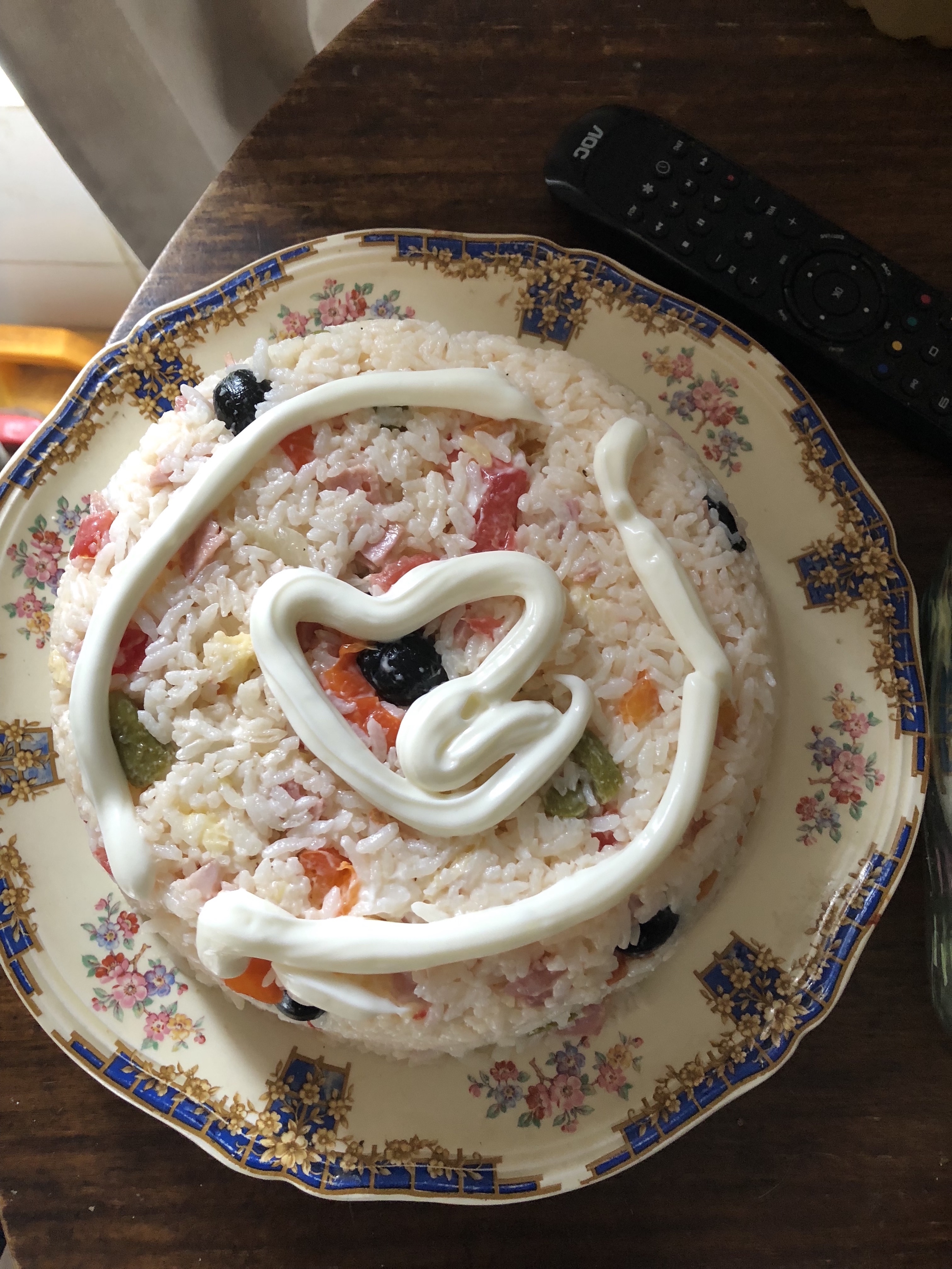 A dish of rice garnished with mayonnaise in the shape of a heart