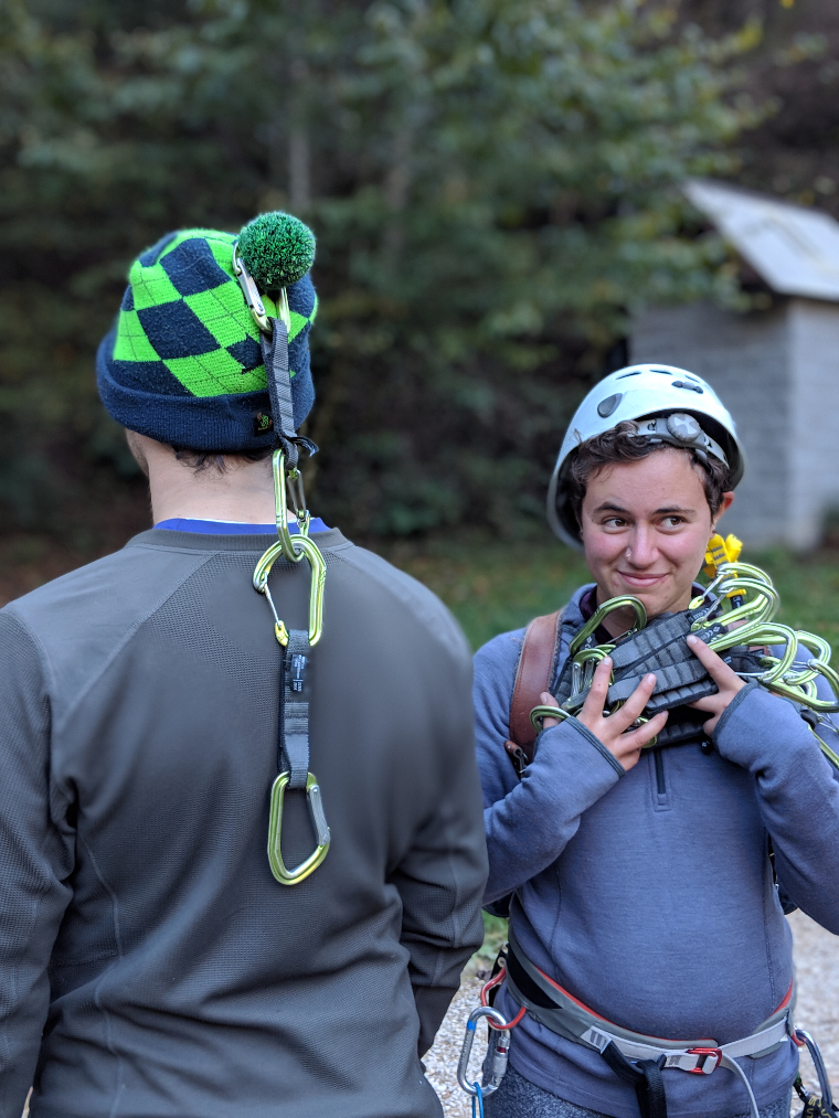 Piper and Paul holding up some carabiners and smiling
