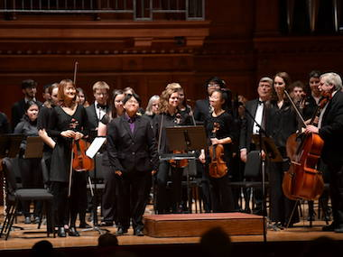 orchestra members stand and prepare to bow following a concert. photo.