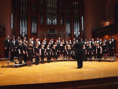 choir members on stage singing. photo.