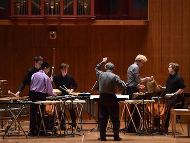 director leads5 percussion players in rehearsal. photo.