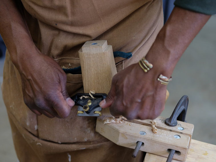 hands working on a wood carving