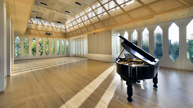 A grand piano in a large sunny room with many windows