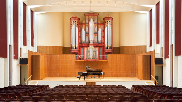 Large stage with grand piano and pipe organ