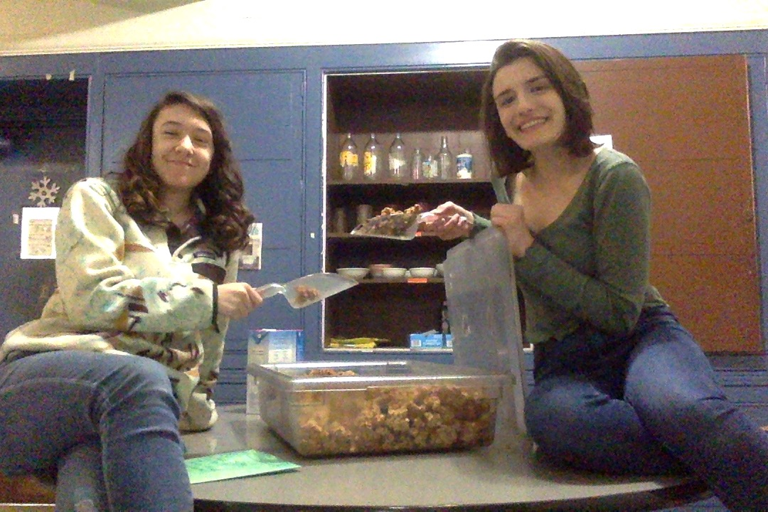 Megan and Lily sit on a table, posing with their muffin man granola. Each holds a scoop of granola, and Megan is also holding the lid. They are smiling