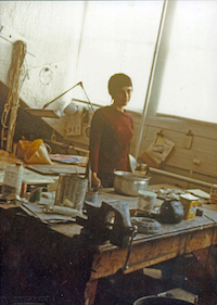 Women standing behind worktable in her art studio.