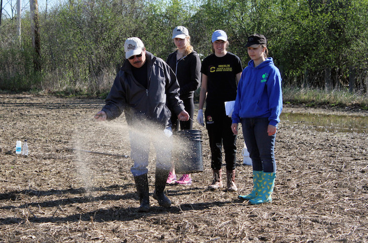 Three students look on as a man throws seeds onto a muddy field
