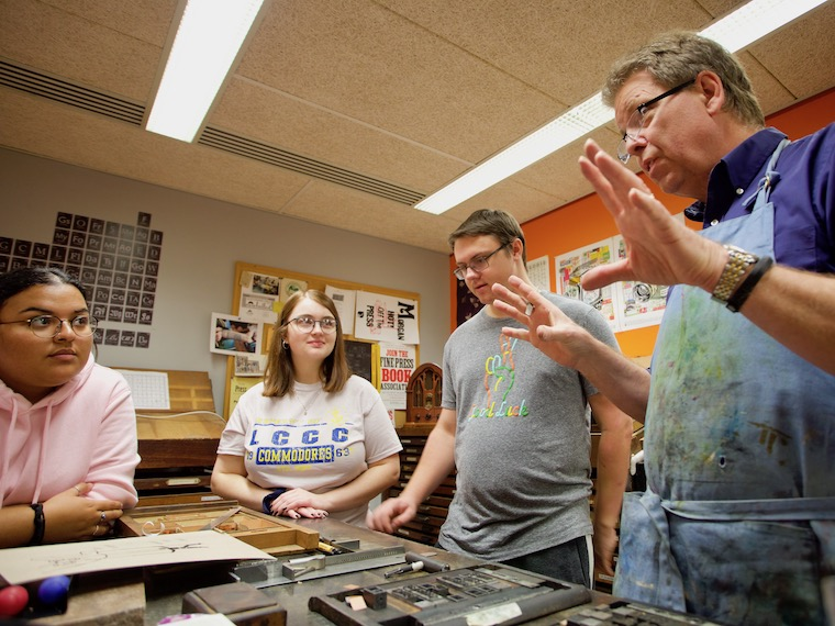 A letterpress teacher leads a workshop with students.