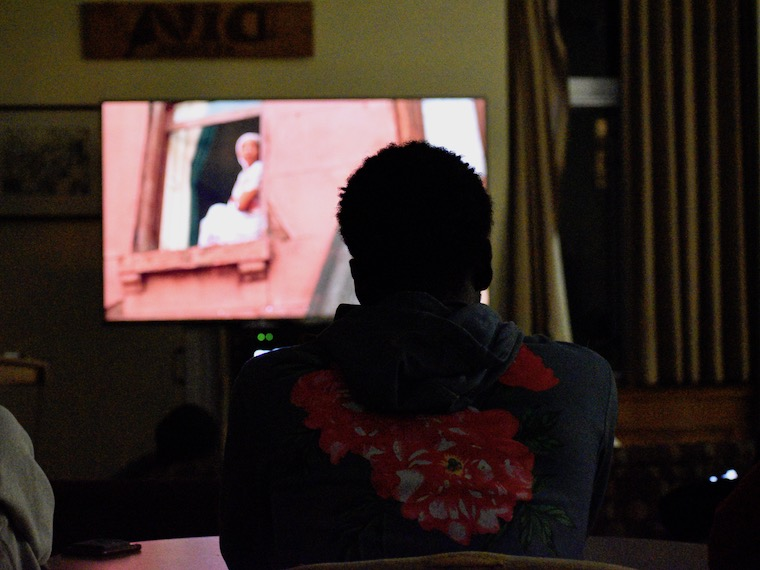 A student watches a movie on television.