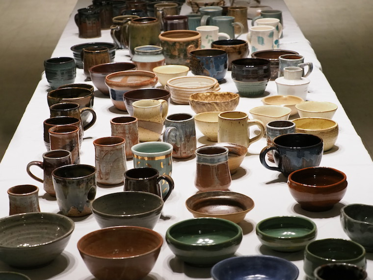 A long table filled with handmade mugs and bowls.