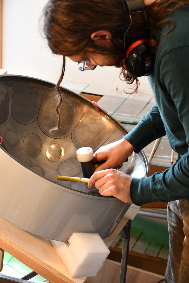 Noah Sanderson working on a steel drum with a hammer. Photo.