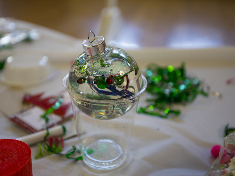 A clear ornament filled with confetti and water sits atop a plastic cup.