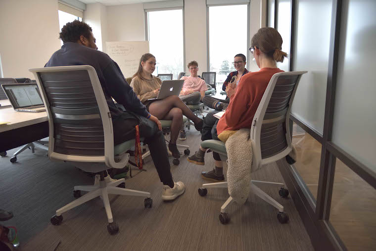 Professor Katherine Thomson-Jones and students sitting in a circle talking in a StudiOC classroom. Photo.