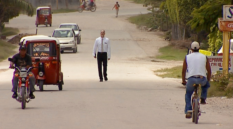 Man walking down a village street.