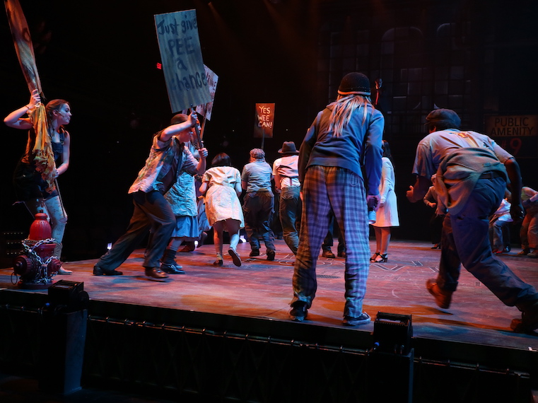 Actors hold give pee a chance signs during a play.