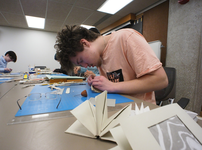 A student makes a book out of handmade paper.